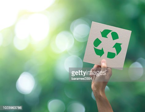 Hand holding recycle symbol on green bokeh background. eco and save the earth concept. : Stock Photo