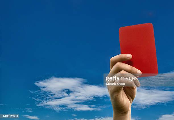Hand holding red card against blue sky