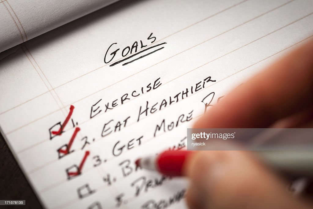 Hand Holding Red Marking Pen Checking Off List of Goals : Stock Photo