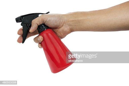 Mão segurando vermelho garrafa pulverizadora de plástico. : Foto de stock