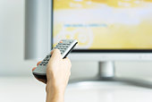 Hand holding remote control, television in background