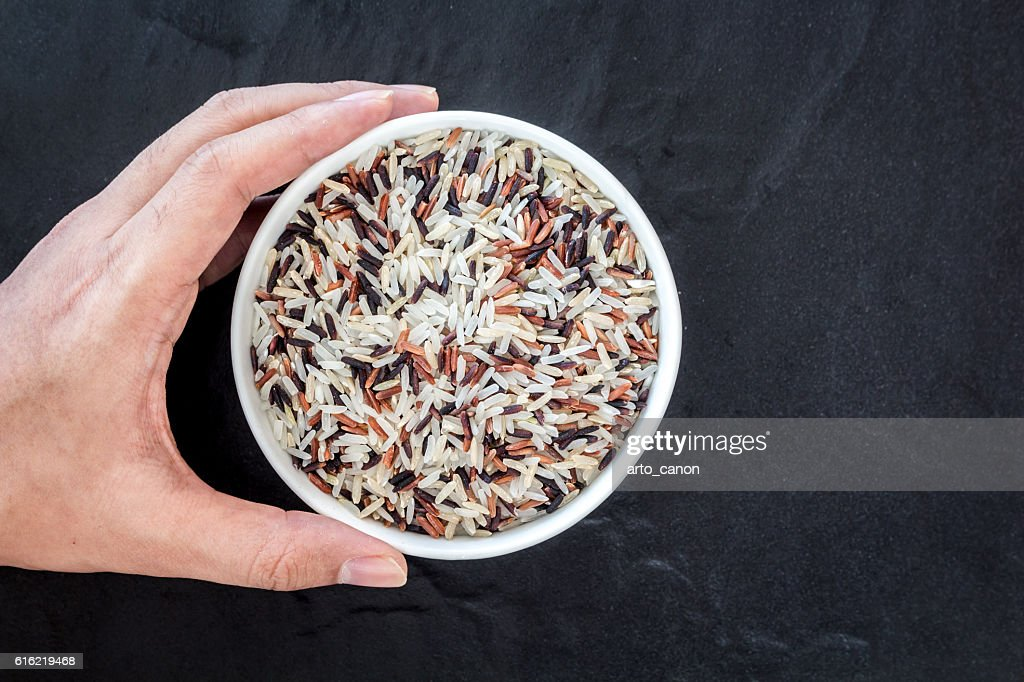 Hand holding rice in a bowl on black background : Stock Photo