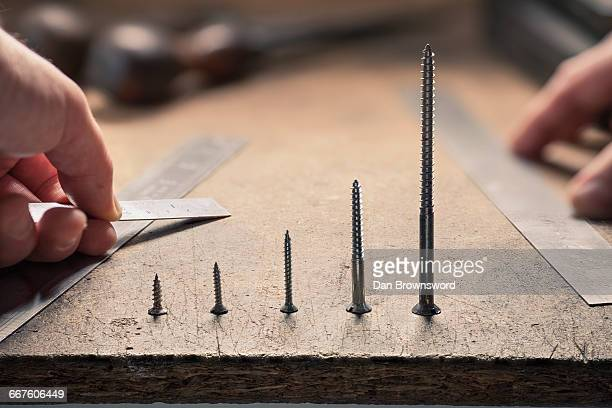 Hand holding ruler, screws standing in a row in ascending order