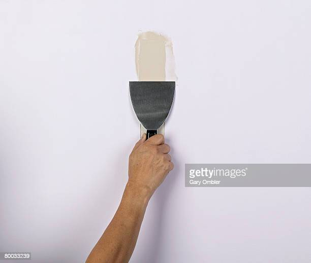 Hand holding scraper to wall
