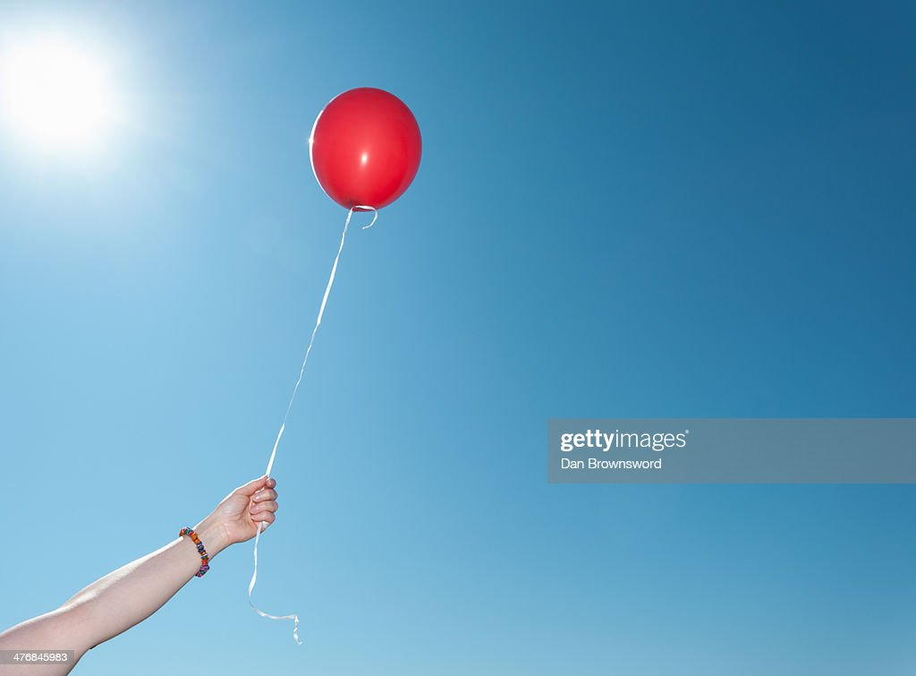 Hand holding single red balloon against blue sky