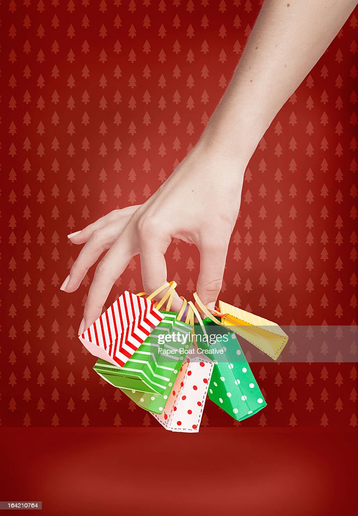 Hand holding small christmas shopping bags : Stock Photo
