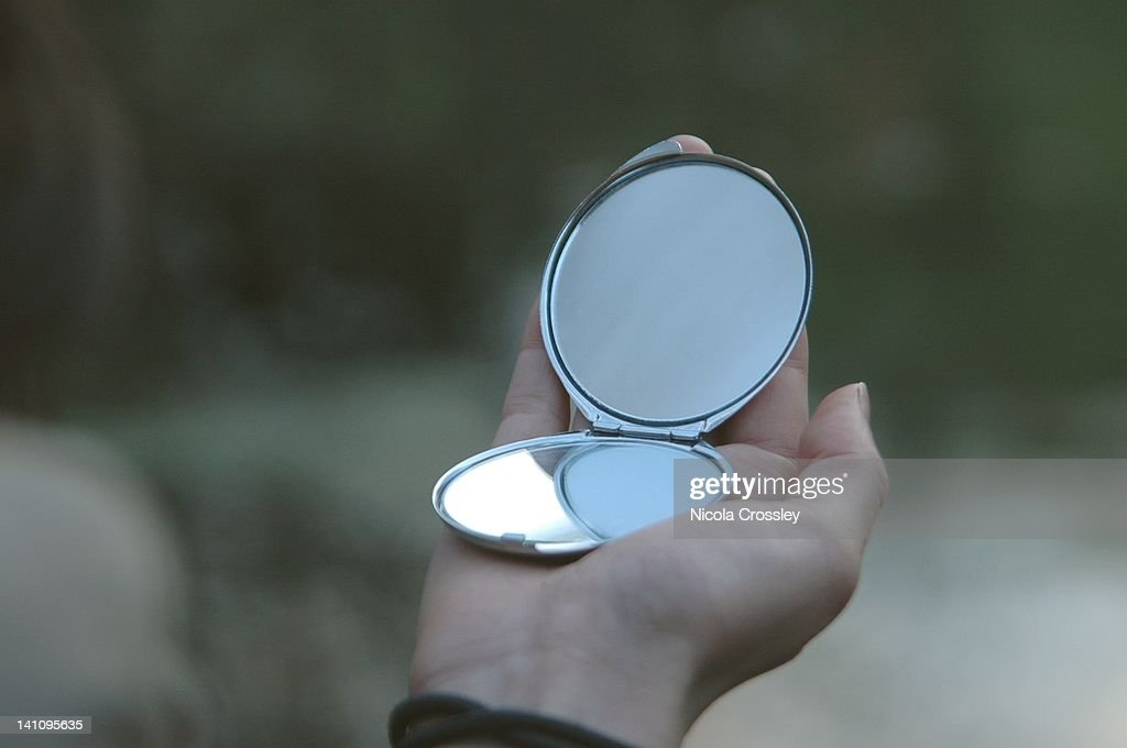 hand holding a mirror. hand holding small silver mirror : stock photo a