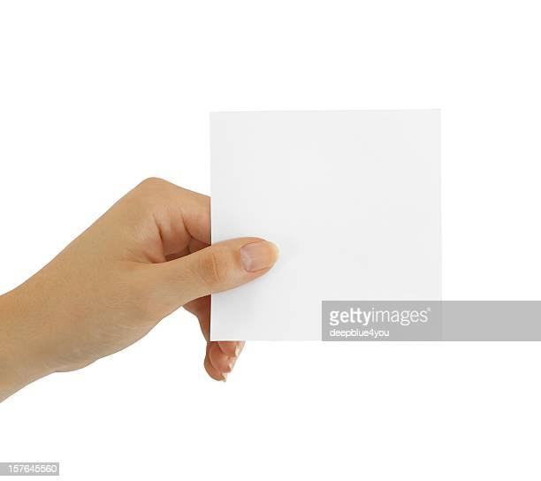 Hand holding small square blank sticky note isolated on white