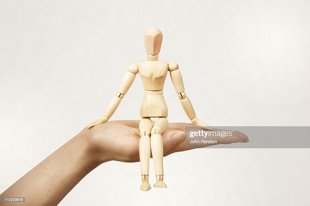 Hand holding small wooden carved figure
