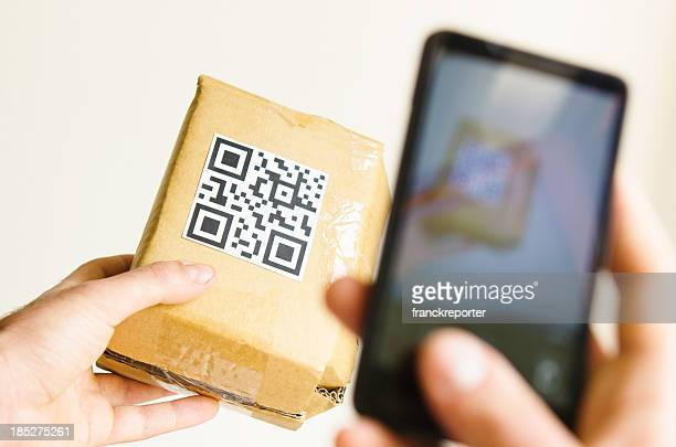 Hand holding smart phone and checking price with QR