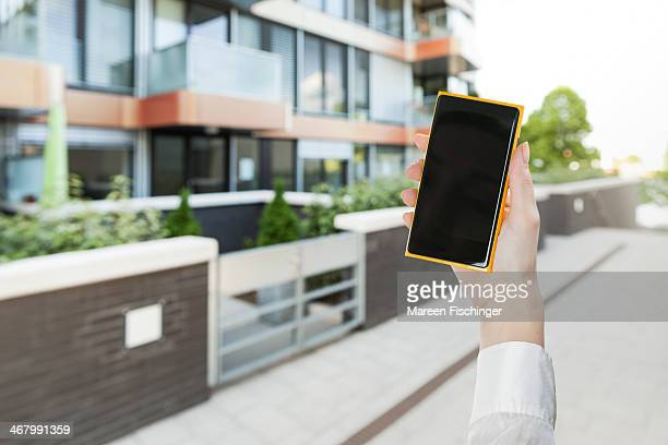 Hand holding smart phone in modern living area