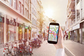 Hand holding smart phone with map app in city