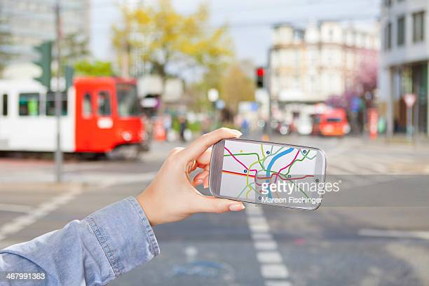 Hand holding smart phone with map in urban area