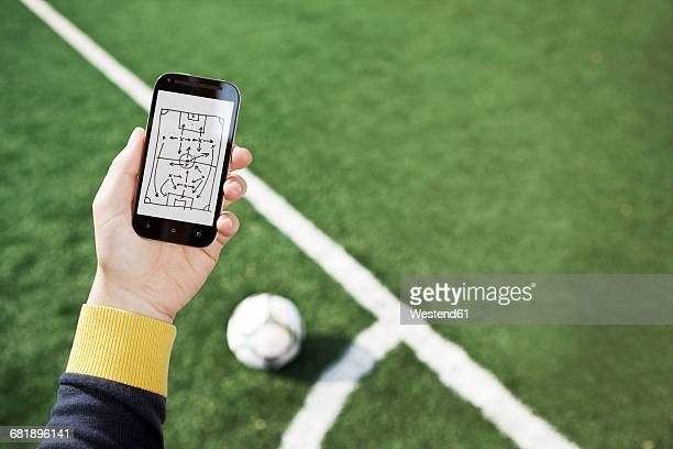Hand holding smart phone with match tactics over soccer field