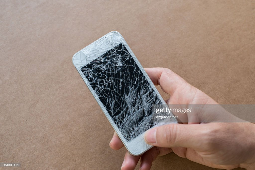 Hand holding smartphone with broken screen : Stock Photo