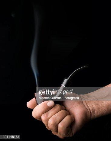 Hand holding smoking pipe