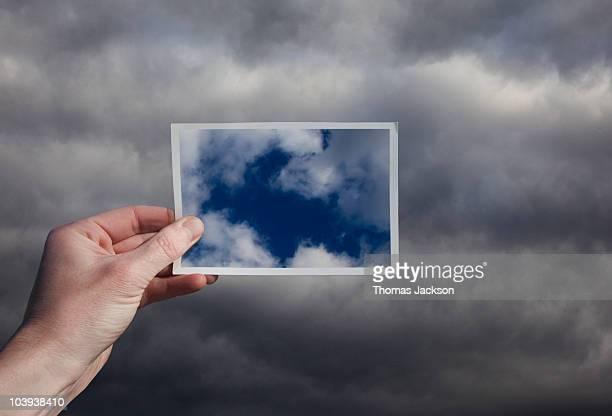 Hand holding snapshot of blue sky