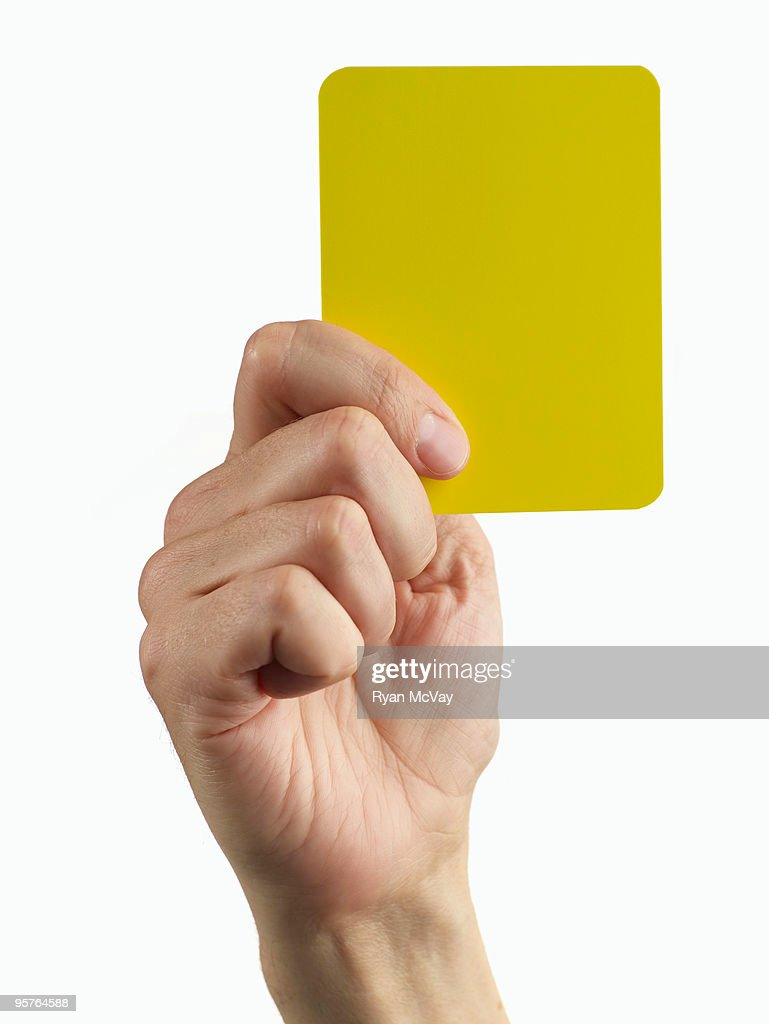 hand holding soccer yellow card