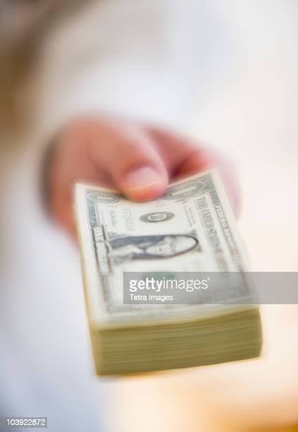 Hand holding stack of money