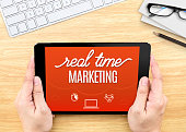 Hand holding tablet with Real-time marketing word on wood table ,Internet marketing concept..