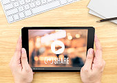 Hand holding tablet with Video sharing on screen on wood table ,Internet marketing concept