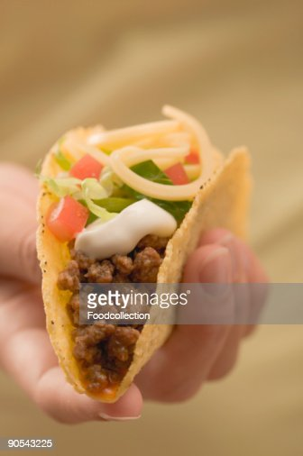 Hand holding taco filled with mince and cheese, close up : Stock Photo