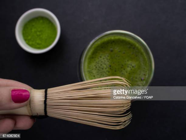 Hand holding tea whisk