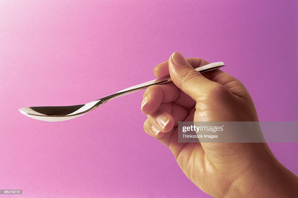 Hand holding teaspoon