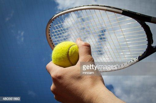 Hand holding tennis ball and racket agaist sky : Stock Photo