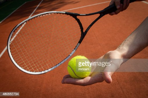 Hand holding tennis racket and ball on court : Stock Photo
