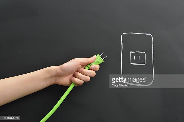 Hand holding the plug, blackboard