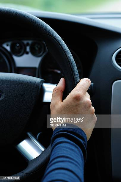 A hand holding the steering wheel