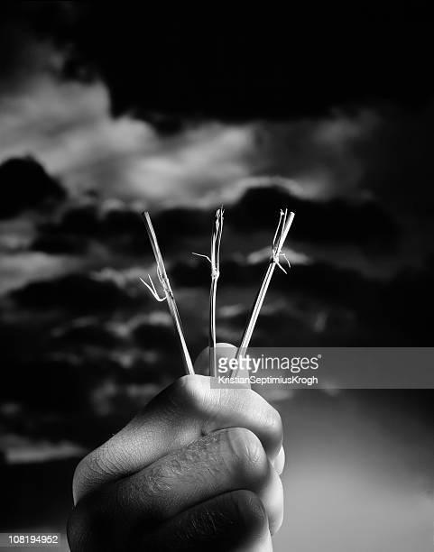 Hand Holding Three Straws to be Drawn