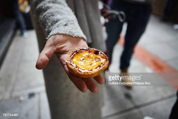 Hand holding traditional egg tart, Macau