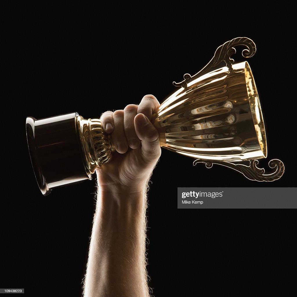 Hand holding trophy on black background : Stock Photo