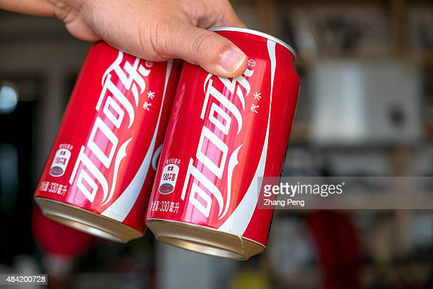 Hand holding two CocaCola cans The strong dollar hit CocaColas overseas operations particularly in China