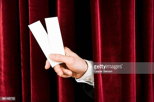 A hand holding two tickets through a red velvet curtain