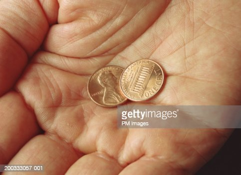 Hand holding two U.S. pennies