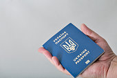 Hand holding Ukrainian biometric passport on white background closeup with copy space