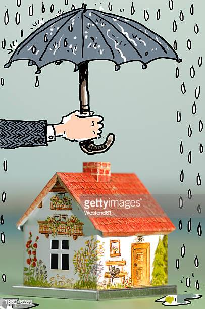 Hand holding umbrella above house, close-up
