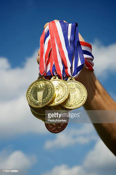 Hand Holding Up a Bunch of Gold Medals Blue Sky
