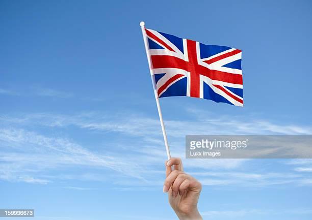 Hand holding up British Flag