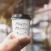"""Hand holding white coffee paper cup with text """"HAPPY MONDAY"""" on blurred window background.Vintage tone, Encouragement and Motivation concept."""