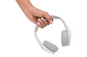 Hand holding white headphones on white background.