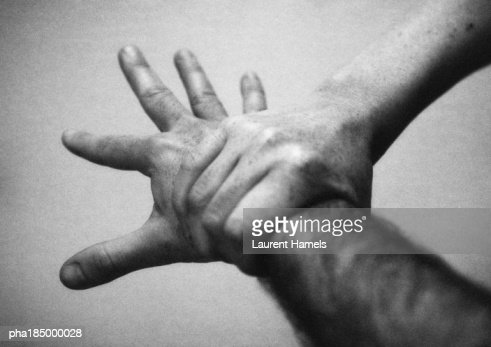 Hand holding wrist, close-up, b&w