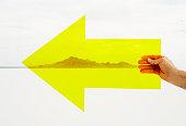 Hand holding yellow arrow in desert.