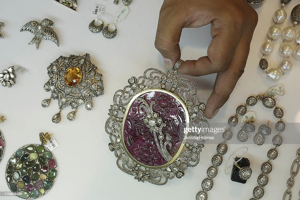 A hand holds a carved Tourmaline Victorian style pendant ( valued at USA$4,000-) among other handmade jewellery on dispaly at Panna Handicraft jewellers at the Hong Kong Jewellery and Gem Fair on June 20, 2013, in Hong Kong. The June Hong Kong Jewellery & Gem Fair runs from June 20 - 23.
