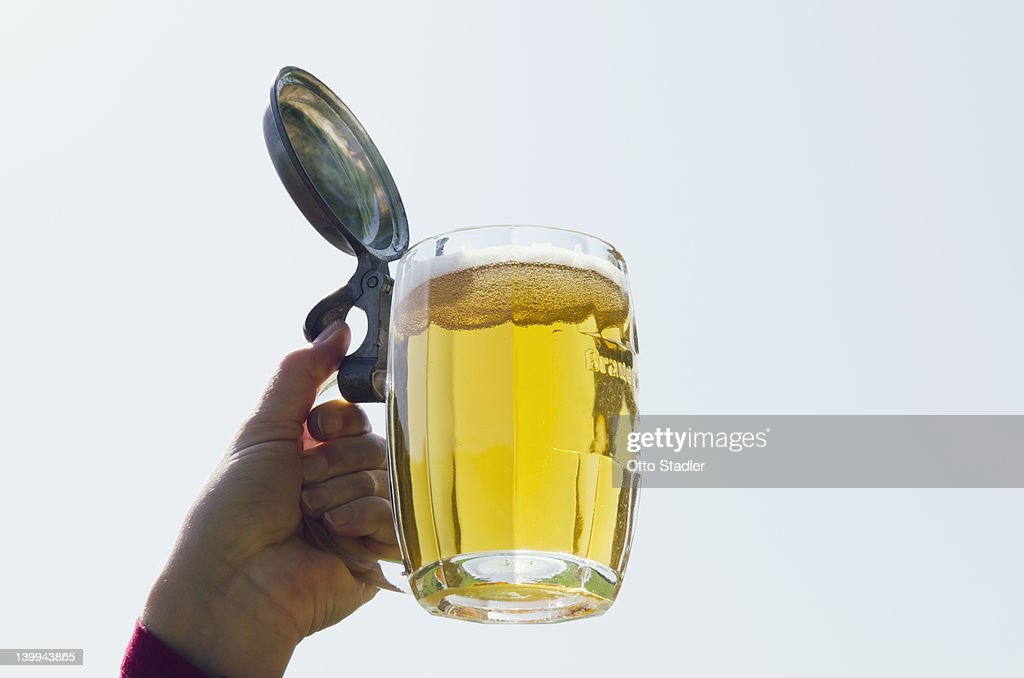 Hand holds a glass of beer in the sky : Stock Photo