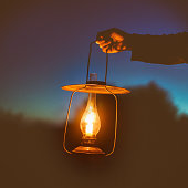 old lamp with a candle illuminates the way on a dark night. dim lightб