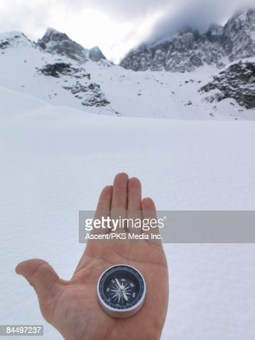 Hand holds compass pointing towards snow mountains : Stock Photo